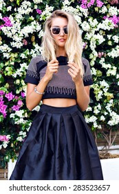 Young gorgeous stunning blonde young woman , wearing stylish outfit, midi skirt, trendy sparkled crop top and sunglasses, posing in floral garden background, beautiful summer day.