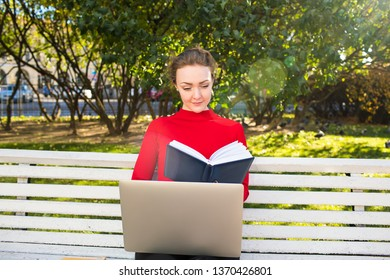 Young gorgeous stylish female clever university student reading book during online eduction on portable laptop computer, sitting in a park in sunny spring day during recreation time in weekend