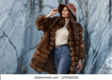 Young gorgeous woman with long wavy brunette hair in brown fur coat standing and posing against gray marble walls at stone quarry. Rich expensive woman
