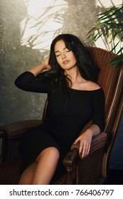 Young gorgeous woman in stylish black dress posing sensually in armchair keeping eyes closed.