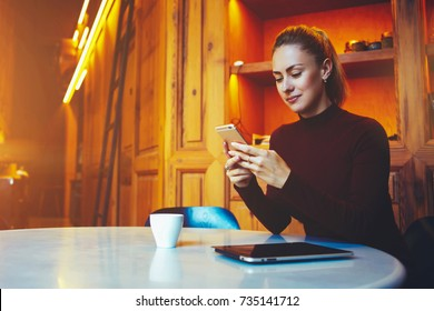 Young gorgeous woman is using smart phone for chat with her friends while is sitting at the table in modern coffee shop interior,attractive female student is resting in contemporary university library