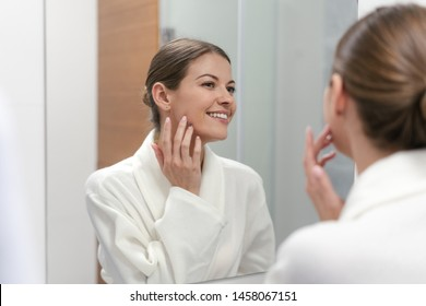 Young and gorgeous woman in white bathrobe standing in bright light bathroom with mirror, holding hand near face, checking skin and smiling wide