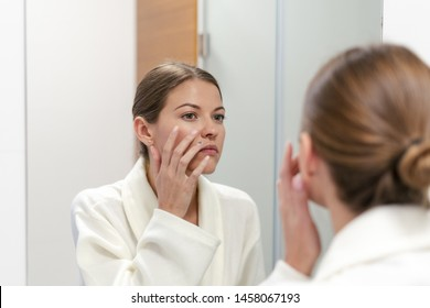 Young and gorgeous woman in white bathrobe standing in bright light bathroom with mirror. She looking at her reflection, with smile, holding hand near face, checking skin