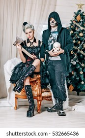 Young gothic couple posing near a Christmas tree. Goth style male model with skull and Goth girl with axe in Christmas decorations.
