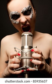 Young gothic singer standing with microphone and screaming