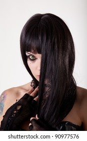 Young gothic woman with yellow eyes and black long hair, studio shot