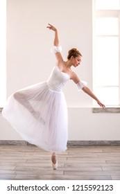 Young graceful ballerina dancing on white studio. Beautiful dancer is training.