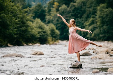 Young graceful ballerina girl balancing on stone in the river.
