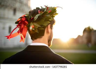 Young graduate boy with the triumphal laurel wreath on his head seen from behind.