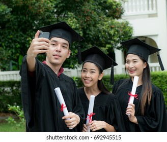 Young graduate taking selfie together,Technology and people concept - group of happy international students in mortar boards and bachelor gowns with diplomas taking selfie by smartphone outdoors.