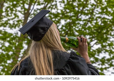 A young graduate woman is drinking champaign to celebrate her graduation