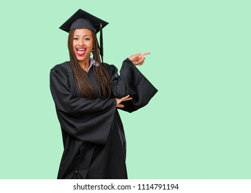 Young graduated black woman wearing braids pointing to the side, smiling surprised presenting something, natural and casual
