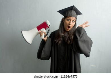 Young graduated indian woman against a wall crazy and desperate, screaming out of control, funny lunatic expressing freedom and wild. Holding a megaphone.