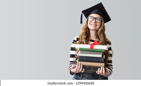 Young graduated student looking away and carrying books on gray background