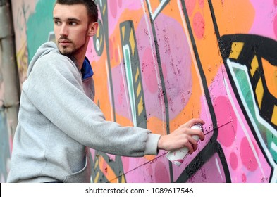 A young graffiti artist looks around while drawing. Vandal tries to be undetected while drawing the picture on the wall. The concept of hooliganism and damage to property