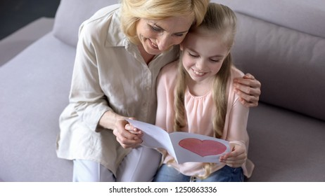 Young grandchild showing handmade greeting card to granny, mothers day, close up