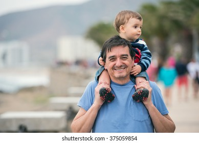 Young grandfather and his grandson walking on the streets
