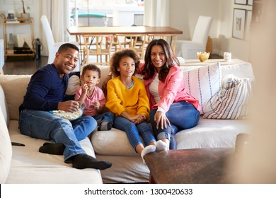 Young grandparents sitting with their grandchildren on sofa in the living room watching TV, selective focus