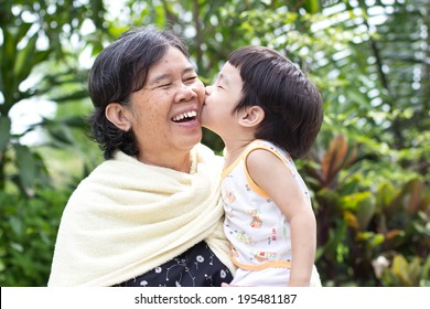 Young grandson giving his grandma a big smooch on the cheek,Asian people