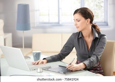 Young graphic designer working on laptop using tablet at home.?