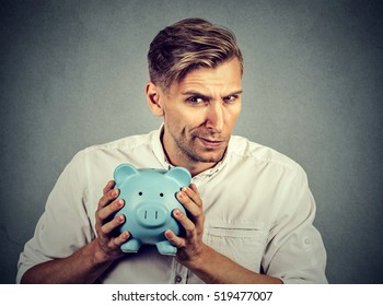 Young greedy stingy business man holding piggy bank isolated on gray wall background