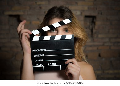 Young green eyes blonde woman actress close up posing with movie clapper behind face