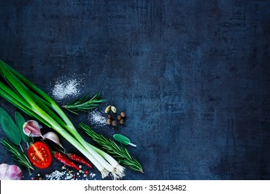 Young green onions with peppercorns, tomato, garlic and rosemary on dark vintage background. Top view. Fresh organic vegetables. Cooking, Healthy Eating or Vegetarian concept.