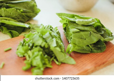 Young green sorrel, sliced for borsch and salad lies on a cutting board, rustic style