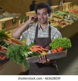 Young Grocery clerk phoning in produce aisle of grocery store