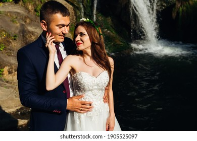 A young groom in a black dress coat with a red tie and a beautiful bride in a white dress are hugging against the backdrop of a cliff, rocks and a river.