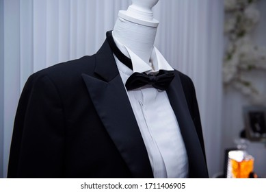 A young groom in a black suit and a black bow tie fix his jacket