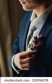 young groom boutonniere in his hand closeup