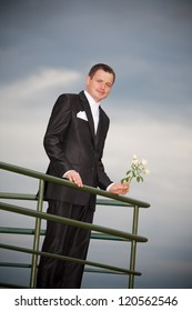young groom with cloudy sky