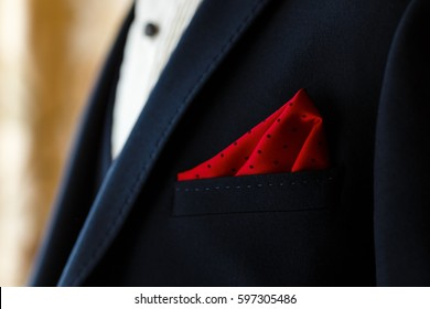 Young groom in dark blue suit with red dotted handkerchief in the pocket. Men's wedding accessories