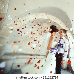 young groom embraces the bride at the festival, everyone is happy, flying confetti. Wedding festive theme