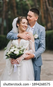 Young groom in a striped blue suit hugs from behind a beautiful bride in a lace white dress in nature outdoors. Wedding portrait of the newlyweds.