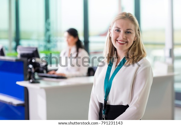 Young Ground Staff Smiling While Colleague Working At Airport Re