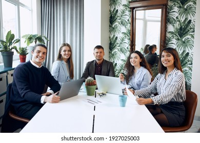 A young group of business people are discussing a new business plan, working on laptops while sitting in a modern office.