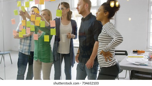 Young group of diverse people standing behind glass wall of office putting bright stickers on it and collaborating on new project.