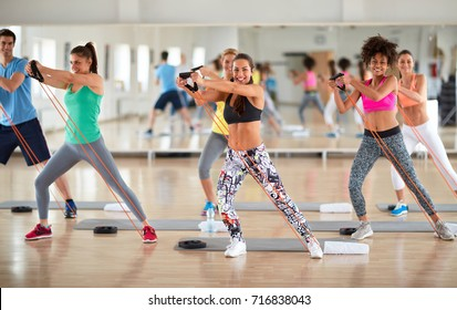 Young group of exercisers doing exercises with resistant rubber in fitness class