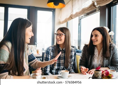Young group of female friends sitting in coffee shop and enjoy coffee talk. Friendship Meeting Togetherness Coffee Concept