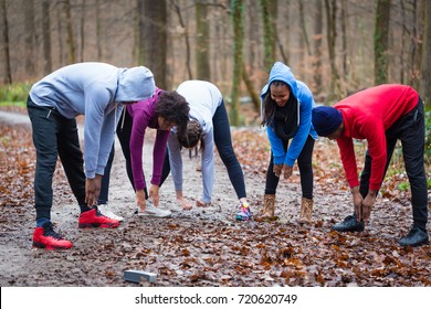 Young group of five people practicing bending exercise for warming up the upper-body outdoors