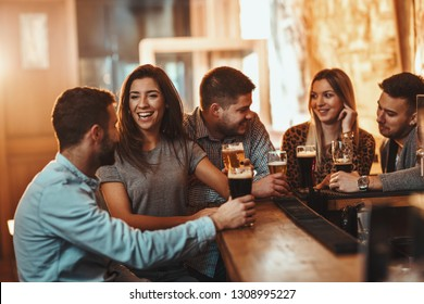 Young group of friends is drinking beer, talking, and having fun in a cafe.