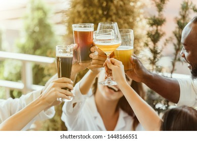 Young group of friends drinking beer, having fun, laughting and celebrating together. Women and men with beer's glasses in sunny day. Oktoberfest, friendship, togetherness, happiness, summer concept.