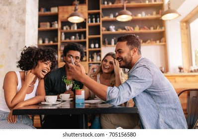 Young group of friends sitting in a cafe and using mobile phone. Young man and women sitting at cafe table and laughing.