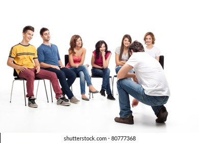 young group of friends, sitting down, listening to man showing