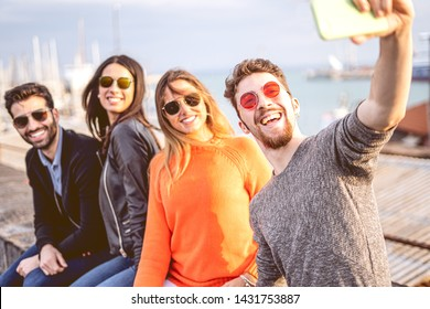 Young group of friends taking selfies sitting on a harbor wall wearing sunglasses. Youth having fun using new technologies concept.