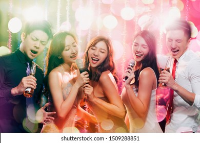 young group holding microphone and singing at karaoke
