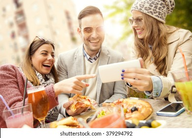 Young group of laughing people eating pizza and having fun
