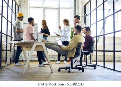 Young group of multicultural colleagues listening skilled female leader explanations during brainstorming session in office,creative dream team members having friendly talk in coworking space
